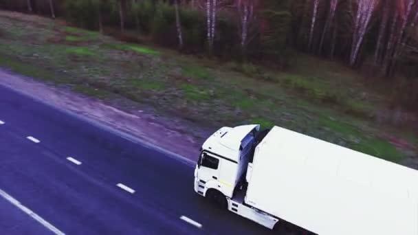 Mnoho nákladních vozidel na dálnici směrem k zapadajícímu slunci. Špička na dálnici nedaleko Bělehrad - Srbsko