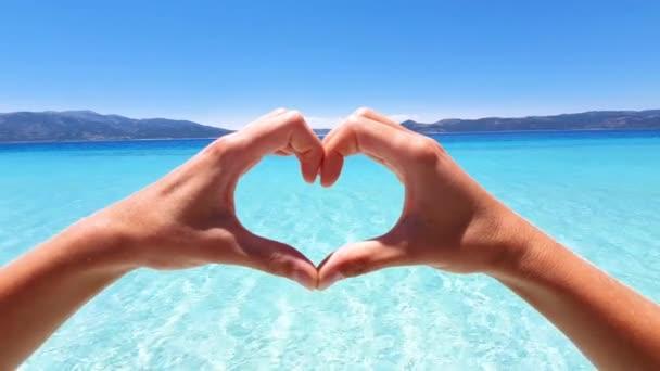 Mädchen lieben tropisches Paradies. Junge Frau am idyllischen Strand formt Herz mit Händen, die Liebe zur Natur und zur Umwelt zeigen - Zeitlupe