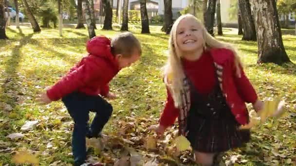 Boy and girl having fun throwing leaves up in autumn park
