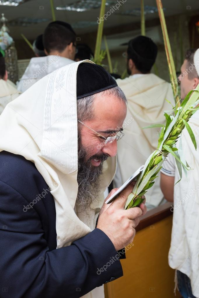 Man holding the four species in the synagogue. Sukkot