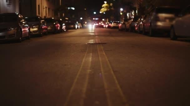 mitten auf der Straße in der Nacht. Kein Verkehr, helle Ampel und geparkte Autos.