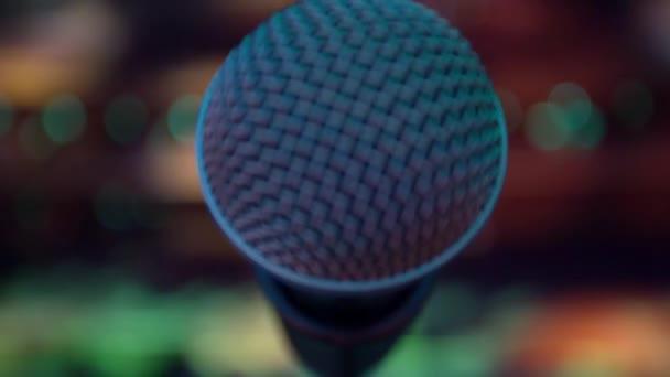 Mikrofon na jevišti, barevné světelné kužele