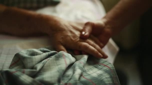 Close Pan of Elderly person holding hands as she lays down in bed