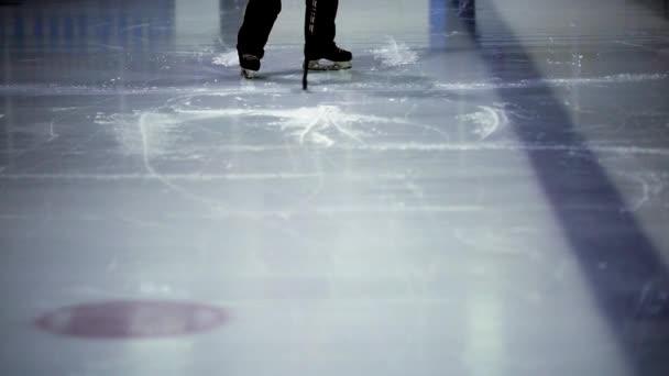 Led bruslaři nohy hrát hokej na zimní stadion