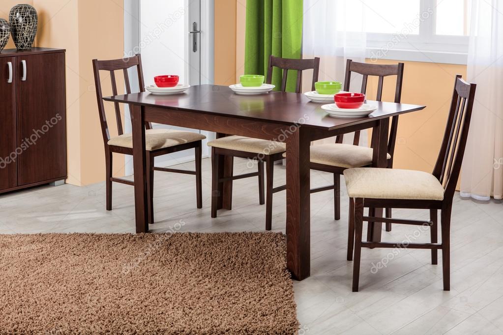 Eenvoudige houten eettafel en stoelen in interieur studio ambi