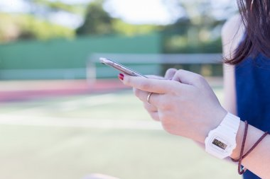 beautiful asian girl using smartphone on tennis court