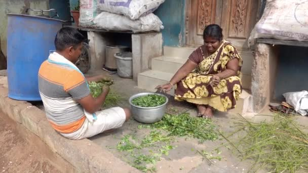 PUDUCHERRY- INDIA - DECEMBER Circa, 2020. Unidentified couple man woman preparing vegetables in street village. An Indian authentic scene about poor people with house to small to cook inside..