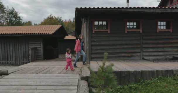 egy anya és gyermeke elsétálnak a Tájház