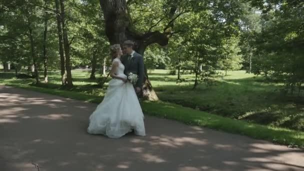 novomanželský pár procházky v parku, drželi se za ruce