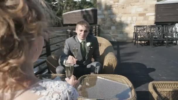 Braut und Bräutigam halten Gläser Champagner sitzen auf der Veranda des Sommer-café