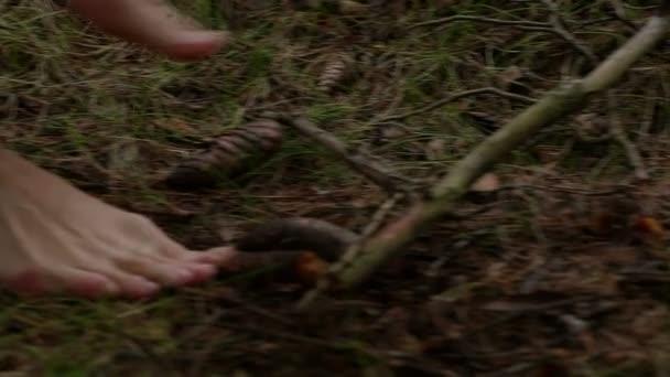 Dívka chodí naboso v lese v plášti