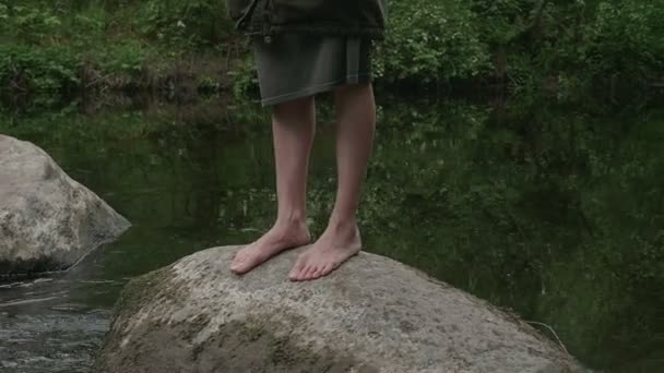 girl walks barefoot in the woods in a cloak