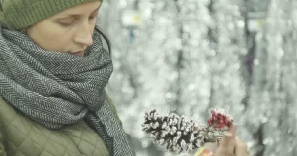 Silvestr, dívka v obchodě vybírá vánoční ozdoby, hračky, koule, kužely