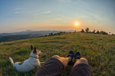 traveller and his dog sitting in the grass and watching the suns