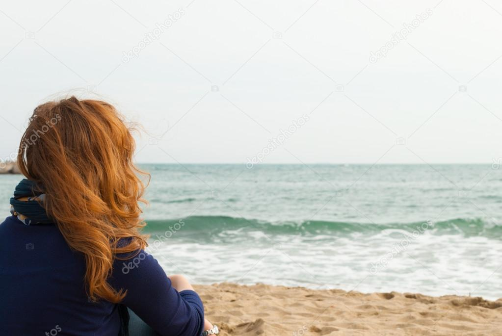 Redhead girl on a Barcelona sand beach looking at the sea