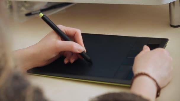designer draws on graphic tablet close up