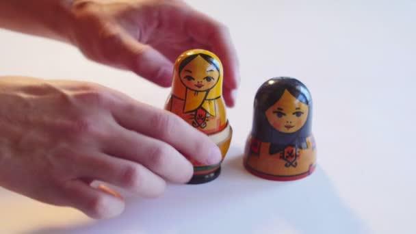 Člověk analyzuje panenka matrjoška na bílém pozadí v rozlišení 4k
