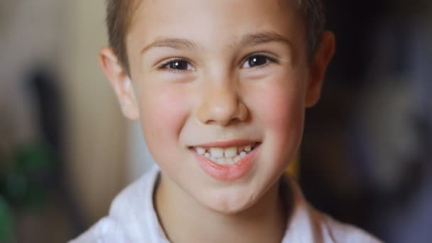 portrait of 8 year old boy with big eyes smiling at the camera in slow-motion