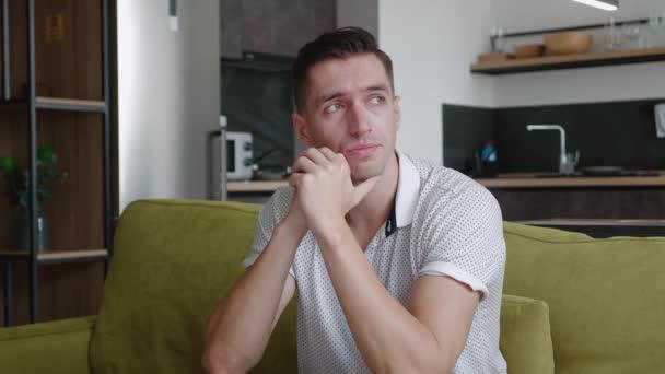 Portrét smutného muže sedícího doma na gauči. Mladí muži v depresi se obávají problémů