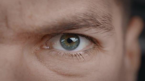 Nahaufnahme Porträt eines wütenden Mannes Auge. Aggressive Männchenaugen blinzeln und blicken ernst in die Kamera.