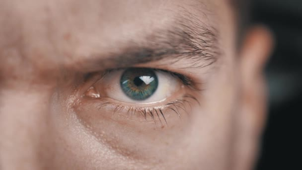 Egy közeli kép dühös emberek szeméről. Agresszív férfi szemek pislognak és komolyan néznek a kamerába..