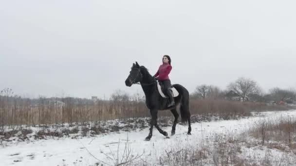 Junge brünette Frau reitet auf einem schönen schwarzen Pferd auf einem Feld oder einem schneebedeckten Bauernhof im Winter. Reiten, Pferdesport. Reiterin auf Pferd geht im verschneiten Freien spazieren