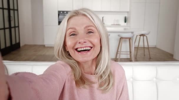 Cheerful senior woman on selfie video conference saying hello facing camera smiling, sitting on sofa at home. Smiling mature lady grandmother holding smartphone do online video call on couch at home.