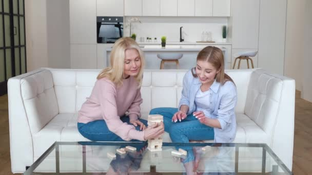 Grownup daughter and her senior mother playing board game, enjoying leisure activity. Multigenerational female family playing block removal game together at home.