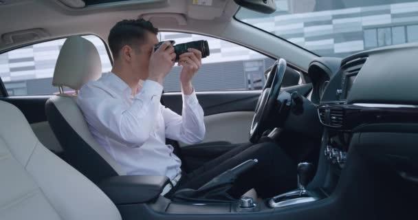 Mann mit Kamera sitzt im Auto und macht Foto mit professioneller Kamera, Privatdetektiv oder Paparazzi-Spionage.