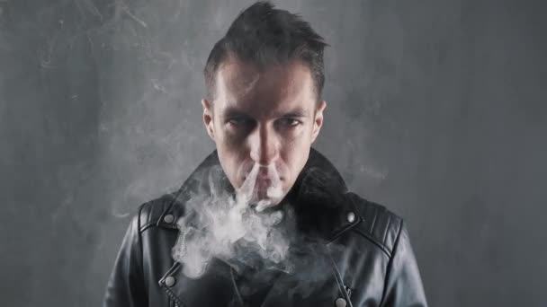 Portrait of brutal smoker man in leather jacket looking at camera