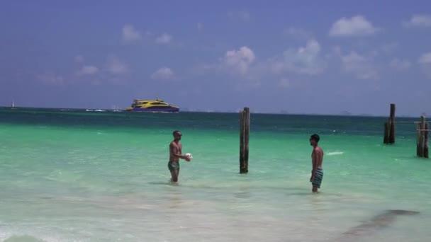 Dva chlapi hrajou plážový volejbal ve vodě. Krásné Karibské moře