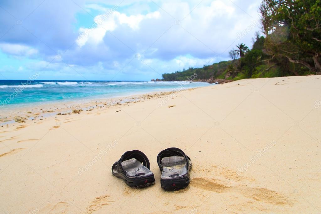 Slippers lying on a remoted beach on Seychelles.