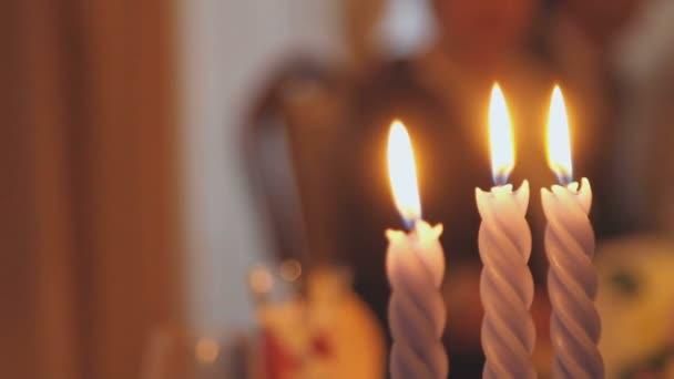 Three burning candles close-up