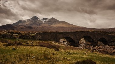 Dark clouds and bridge on Sligachan with Cuillins Hills in the background, Scotland, United Kingdom