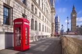 Hagyományos vörös brit telefonfülke, Big Ben és emeletes busz a háttérben egy napsütéses délutánon, a blue sky és clouds - London, Egyesült Királyság