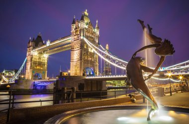 The lady and the dolphin fountain with Tower Bridge at night, London, UK