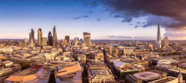 Panoramic skyline of the famous business district of London at sunset with dark clouds - London, UK