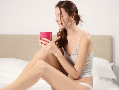 beautiful young woman in the bed with pink cup