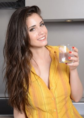 happy smiling woman in the kithen with glass of water