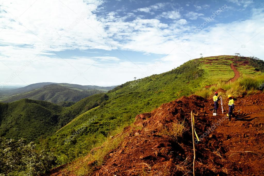 Mining construction workers surveying mountain top in Africa