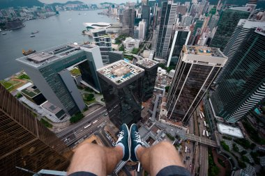 sitting on the edge of the roof of a skyscraper in modern part of Hong Kong