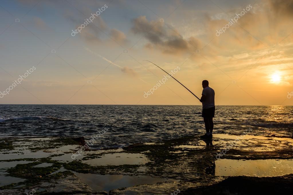 man fishing on sea coast