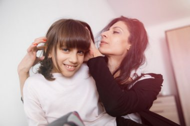 Young mother and daughter sitting on the sofa