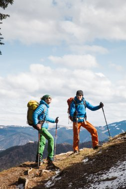 Two hikers in winter mountains installing tent
