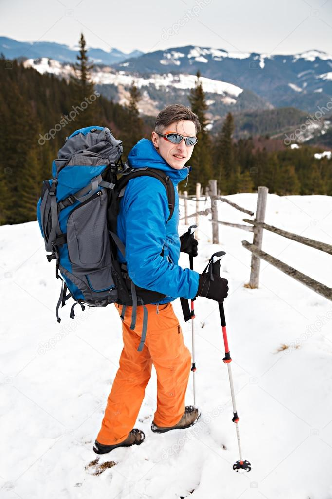 Hiker with huge backpack in winter mountains
