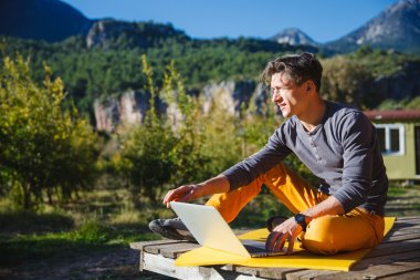 Freelancer working on computer over the mountain landscape