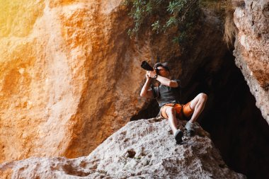 Male photographer on the cliff shooting on dslr camera