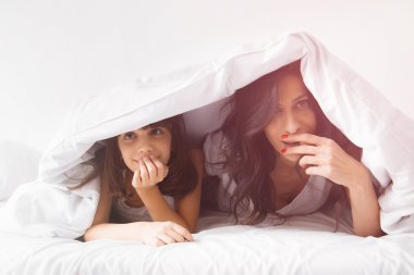 Portrait of brunette long hair mother and daughter under the duvet together in soft morning light on white linen bed. Concept of happy family living, relaxation, comfort, fun. Top view. stock vector