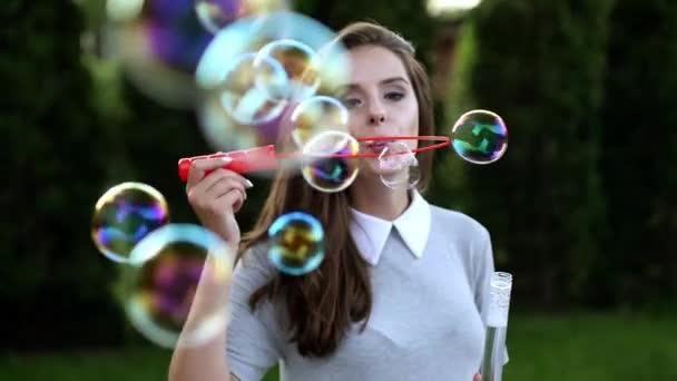 krásná mladá dívka foukání bublin