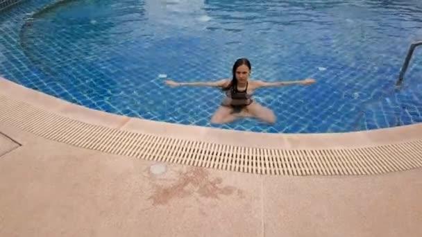 Mladá žena plavala v otevřeném modrém bazénu. Venkovní aktivity. Zdravý životní styl. Horní pohled letecké video 4k.